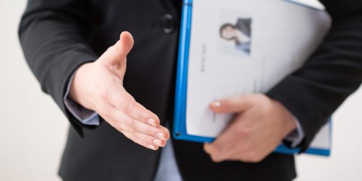 履歴書を持って手を差し伸べてくる女性