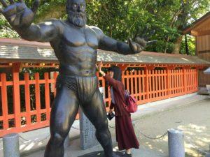 福岡県の住吉神社に参詣したとき、古代力士像の筋肉に触ろうとしている写真です